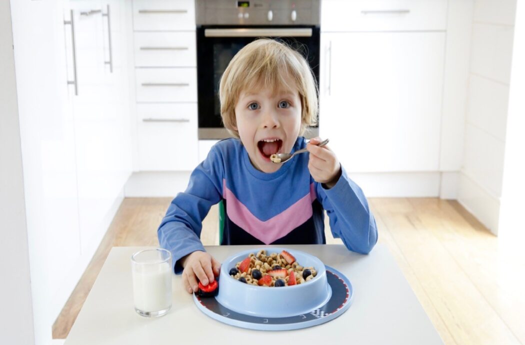 Child eating from Munchy Play plate with in-built toy.